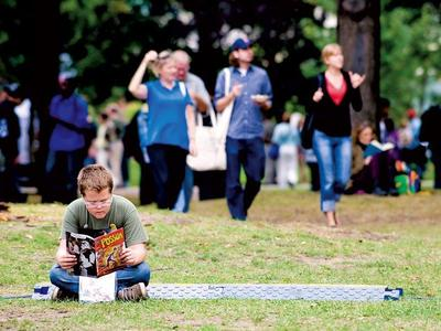 Courtesy of Metro News: Dante Petitti reads amid festival-goers at The Word on The Street literary festival, held in and around Queen's Park. He was reading a comic called The Possum, by Blair Kitchen. This is the festival's 20th year.